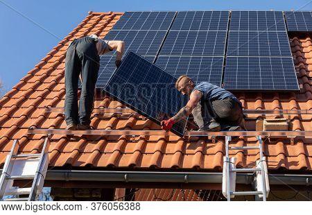 Ochojno, Poland - April 8, 2020: Workers Installing Solar Electric Panels On A House Roof In  Ochojn