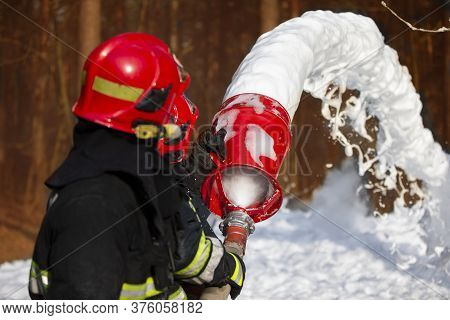 Firefighters Extinguish A Fire. Rescuers With Fire Hoses With Foam.