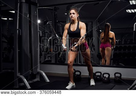 Fitness Girl Workout In The Gym On The Simulator, Makes Spreading Exercises With Her Hands. Sports M