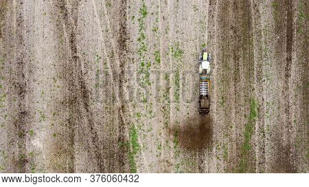 A Tractor With A Trailer Fertilizes The Field With Natural Fertilizer-manure. Aerial View.