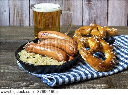 Oktoberfest Concept. Traditional German Sausages Bratwurst With Sauerkraut, Beer, And Pretzels On Th