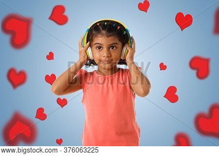 Music, Childhood And Technology Concept- Little Indian Girl With Headphones Over Blue Color Backgrou