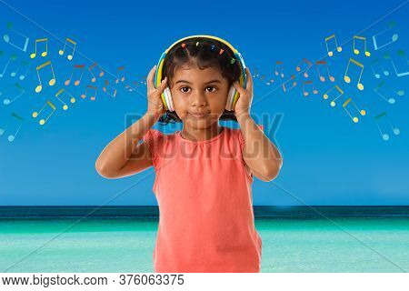 Music, Childhood And Technology Concept- Little Indian Girl With Headphones Over Sea View Background
