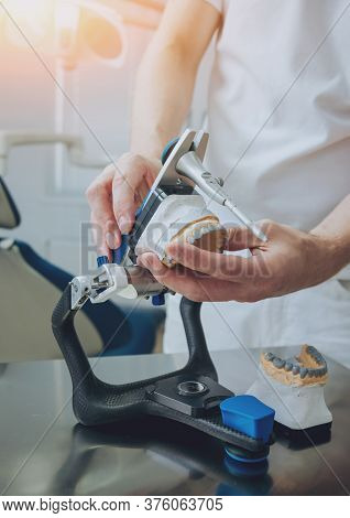 Dental Technician Working With Articulator In Dental Lab