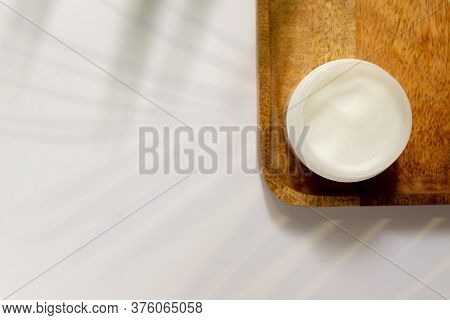 White Jar Of Face Cream On A Wooden Tray. White Background, Top View, Tropical Leaves. Concept Of Na