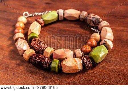 Beads Made Of Ural Jasper On Wooden Background