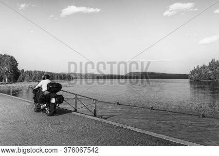A Man On A Motorbike By A Piear In A Beautiful Lakeside Landscape At The Central Finland.