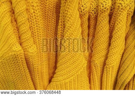 Several Knitted Warm Yellow Pullovers With Different Patterns Weigh On A Hanger.