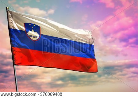 Fluttering Slovenia Flag On Colorful Cloudy Sky Background. Slovenia Prospering Concept.