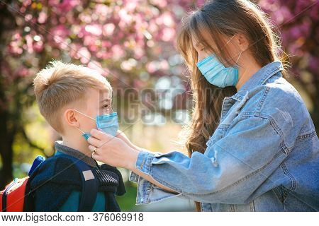 Mother Puts A Safety Mask On Her Son. Cute Boy With A Backpack Going To School. Back To School Conce
