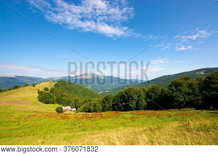 Green Meadow Scenery On The Hill. Fluffy Clouds On The Blue Sky Above The Distant Mountain. Bright S