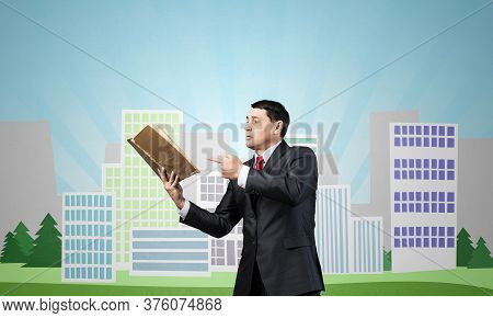 Senior Businessman Finger Pointing Into Open Book. Adult Man In Business Suit And Tie Standing On Ci