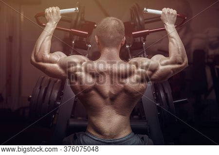 Bodybuilder Strong Man Pumping Up Biceps Muscles.