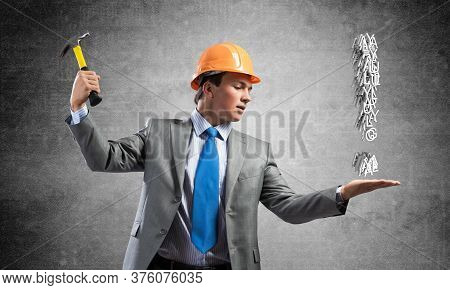 Businessman Going To Crash With Hammer Exclamation Mark. Young Handsome Man In Business Suit And Saf