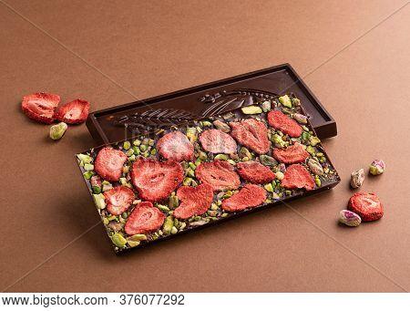 Chocolate Dark Belgian Bar With The Addition Of Pistachio Strawberries On Brown Background. Dessert