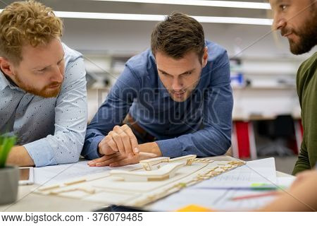 Team of architects and engineers working on house model scale. Partners in an architectural firm working together on a urban building model scale at office. Business men making model house at office.