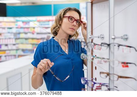 Mature woman trying on glasses she wants to buy in optician store. Mid adult woman trying spectacles in optic store . Undecided customer choosing between two pairs of glasses while looking at mirror.