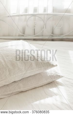 White Linen Textile Bedclothes. Pile Of Pillows. Cozy Bedroom Interior And Beautiful Morning Light.