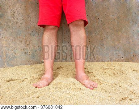 Male Feet In The Sand. Legs Of A Man In Red Shorts. Male Feet On The Yellow Sand Of Ericeira Beach,
