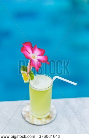 Fresh Cold Fruit Juice On Poolside. With Straw, Slice Of Lime And Tropical Flower