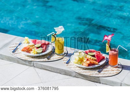 Two Plates With Fresh Fruit And Two Juice With Slice Orange. Healthy Breakfast On Poolside In Hotel.