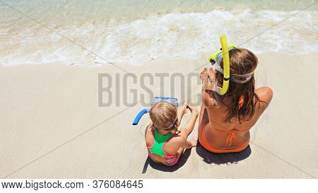 Happy Family - Mother, Baby Girl In Snorkeling Mask Sit On White Sand Beach Of Tropical Island. Look