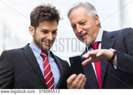 Senior manager showing something on a smartphone to his younger colleague