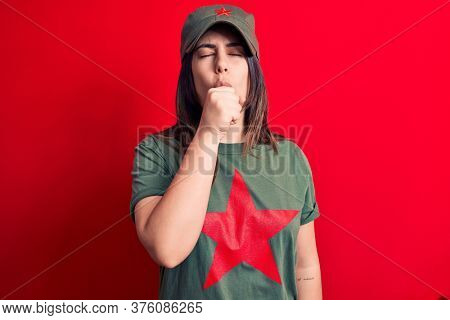 Young beautiful brunette woman wearing cap and t-shirt with red star communist symbol feeling unwell and coughing as symptom for cold or bronchitis. Health care concept.