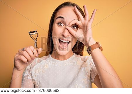 Young beautiful woman using eyelash curler standing over isolated yellow background with happy face smiling doing ok sign with hand on eye looking through fingers