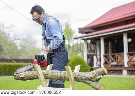 Man Sawing Wood In Coutryside On Backyard. Close Up Saw And Lumberjack Cutting Trees Outdoors. Woodc