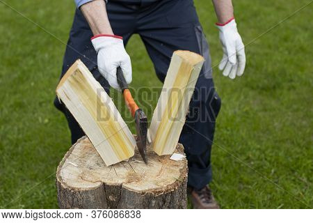 Close Up Strong Man Lumberjack Chopping Wood With Sharp Ax On Wooden Hemp Sawdust Fly To Sides. Powe