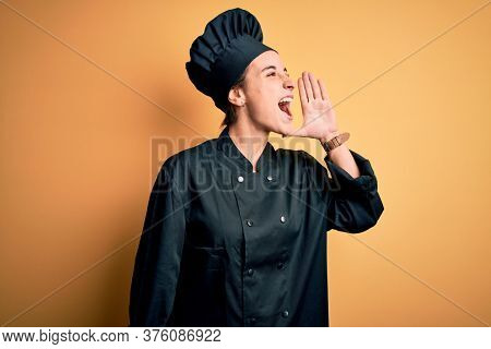 Young beautiful chef woman wearing cooker uniform and hat standing over yellow background shouting and screaming loud to side with hand on mouth. Communication concept.