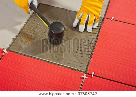 Worker With Hammer And Glass Tile Demonstrates Adhesive