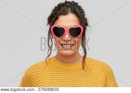 summer, valentine's day and eyewear concept - portrait of happy smiling young woman with pierced nose in pink heart-shaped sunglasses over grey background