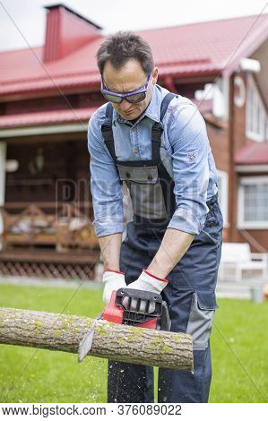 Man Sawing Wood In Coutryside On Backyard. Lumberjack Cutting Trees Outdoors With Chainsaw. Woodcutt