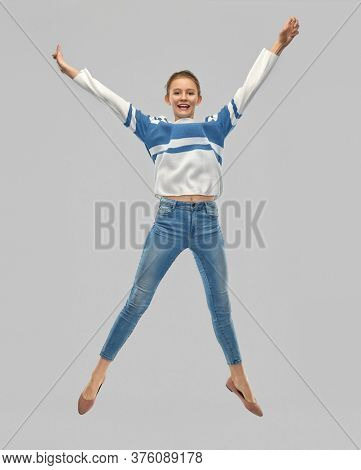 people concept - smiling teenage girl in pullover jumping over grey background