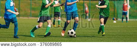Horizontal Image Of Soccer Competition. Junior Level Football Match. Players Running And Kicking Cla
