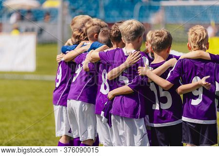 Sporty Boys In A Team On The Field. Group Of Children In Purple Shirts Huddling Before The Final Gam