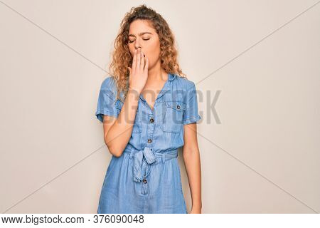 Young beautiful woman with blue eyes wearing casual denim dress over white background bored yawning tired covering mouth with hand. Restless and sleepiness.