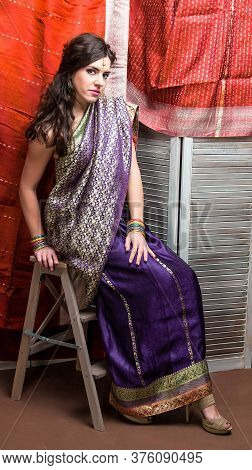 The Young Dark-haired Woman In The Rich Indian Saris And Colored Bracelets Looks Thoughtfully Sittin