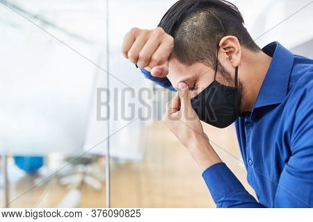 Business man with face mask because of Covid-19 in the office suffers from overload or burnout