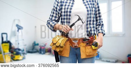repair, construction and building concept - close up of woman or builder with hammer and working tools on belt over utility room background