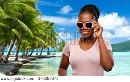 summer holidays, travel and valentine's day concept - happy african american young woman in heart-shaped sunglasses over tropical beach background in french polynesia