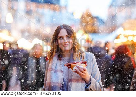 Beautiful Young Woman Having Fun On Traditional Christmas Market During Strong Snowfall. Happy Girl