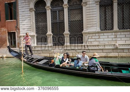 Venice, Italy - Sep 13, 2015: Five Tourists Of Asian Ethnicity Sitting In The Gondola With A Gondoli