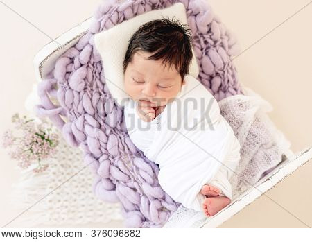 Funny newborn resting on tiny bed with pillow, top view