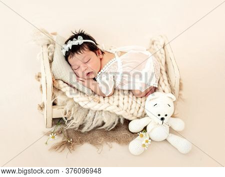 Nice newborn in lace dress sleeping on small bed