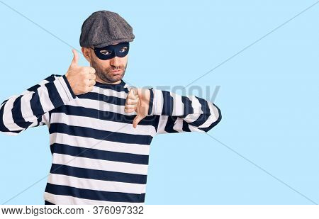 Young handsome man wearing burglar mask doing thumbs up and down, disagreement and agreement expression. crazy conflict
