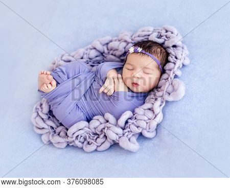 Cute newborn with floral rim wrapped in purple blanked