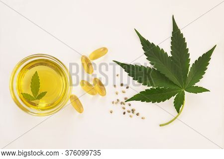 Hemp Extraction Oil In Bowl And Capsulesnear Cannabis Fresh Leaves And Seeds On White Background.